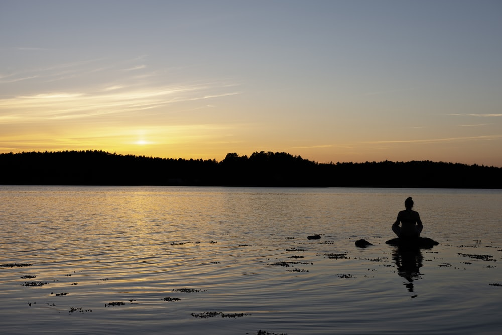silhouette of person riding on boat on water during sunset