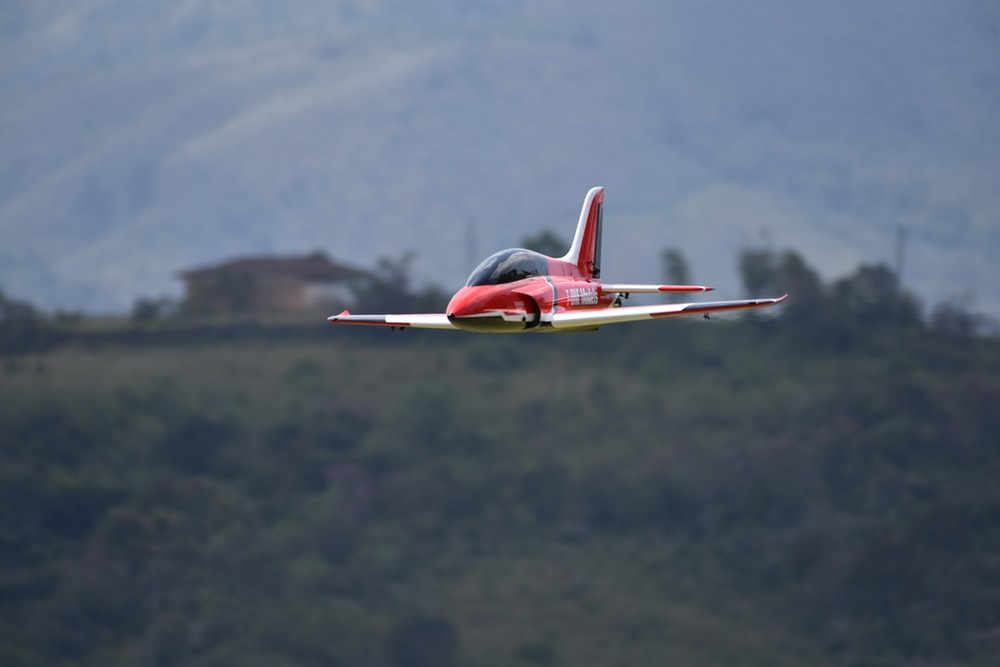 red and white airplane flying over green mountains during daytime