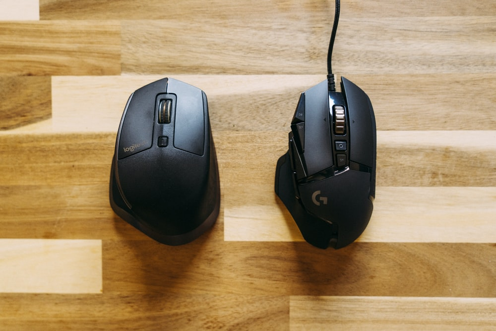 black corded computer mouse on brown wooden table