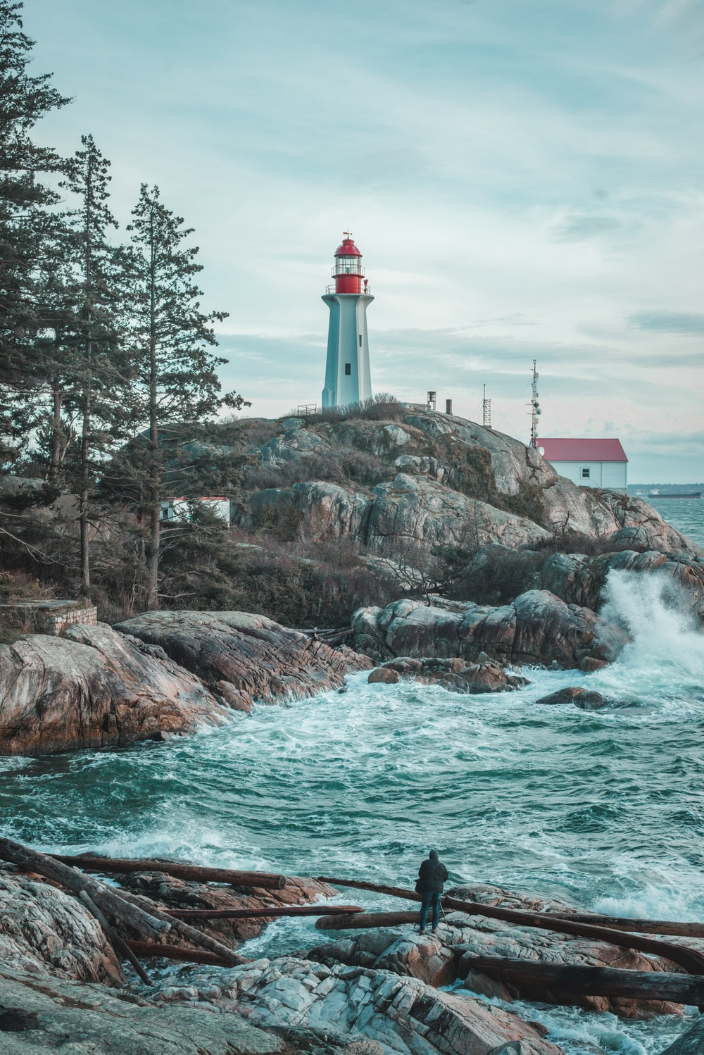 white and red lighthouse on brown rock formation near body of water during daytime