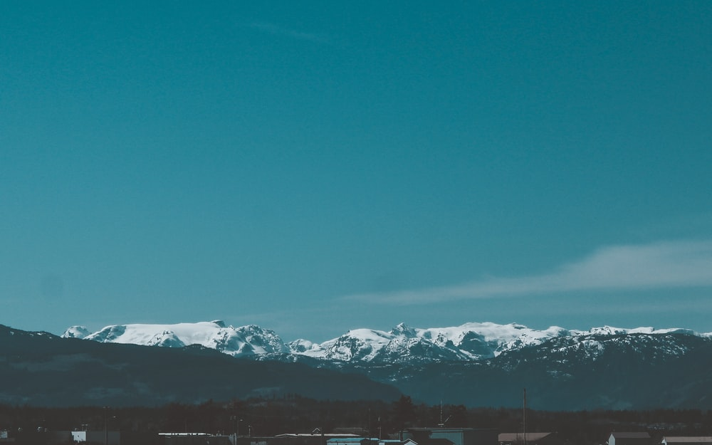 snow covered mountains under blue sky during daytime