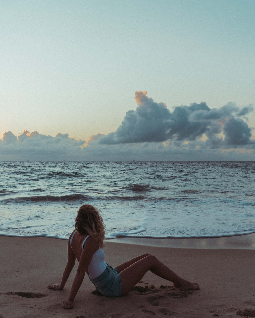 woman in blue bikini sitting on beach shore during daytime