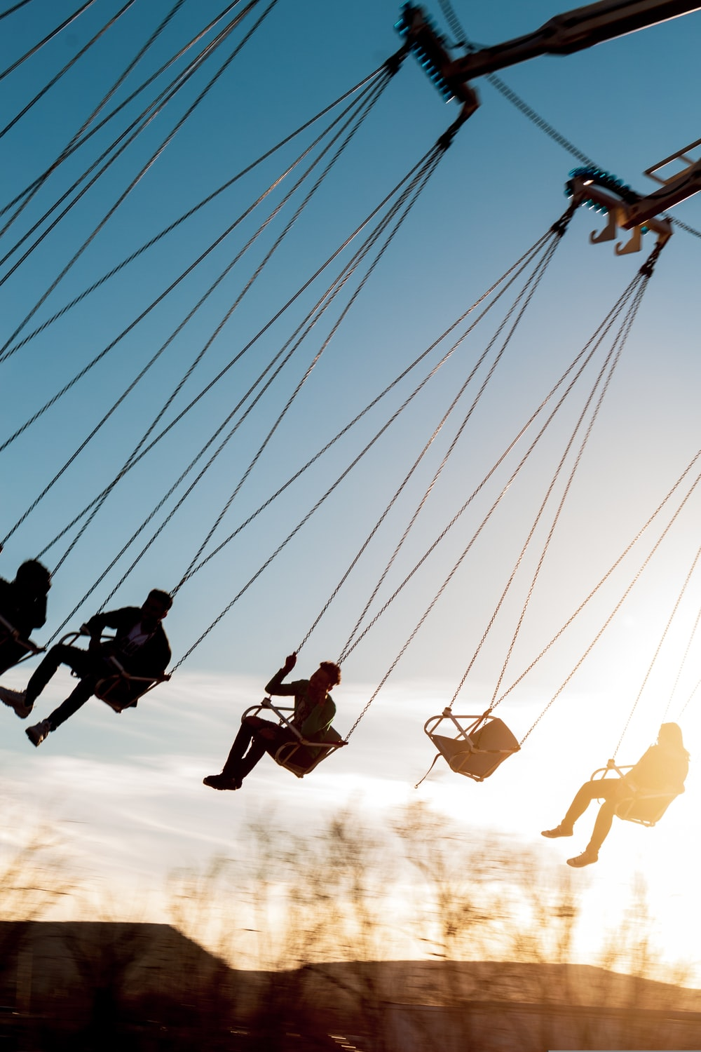 silhouette of people riding swing during daytime