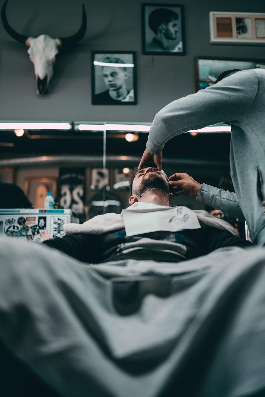 man in black long sleeve shirt lying on hospital bed