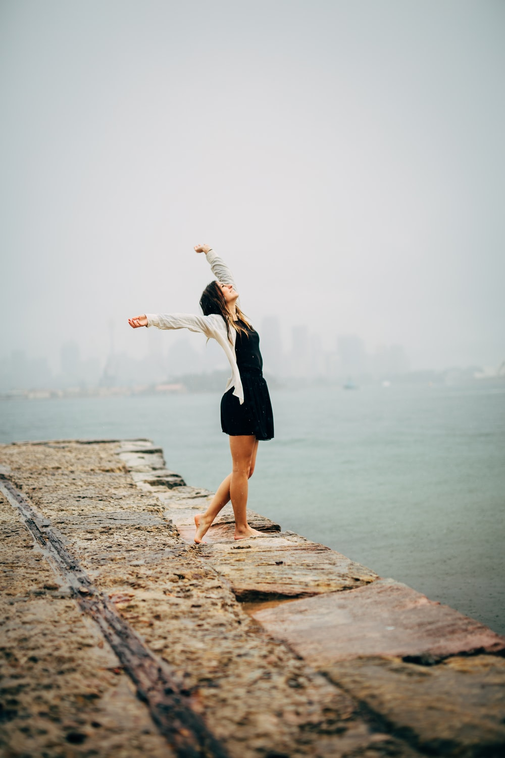 woman in black dress standing on concrete dock during daytime