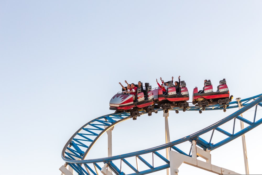 people riding red and white roller coaster during daytime