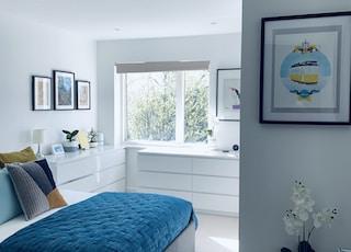 blue bed linen near white wooden framed glass window