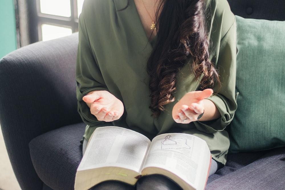 woman in green coat reading book