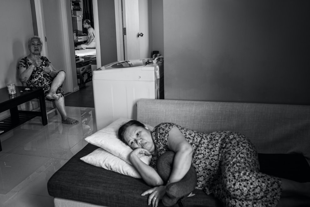 woman lying on bed in grayscale photography
