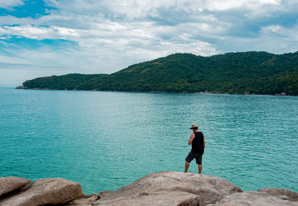 man in black shirt standing on rock near body of water during daytime