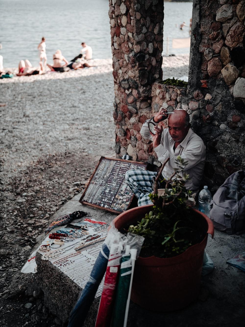 man in white dress shirt sitting on brown wooden bench