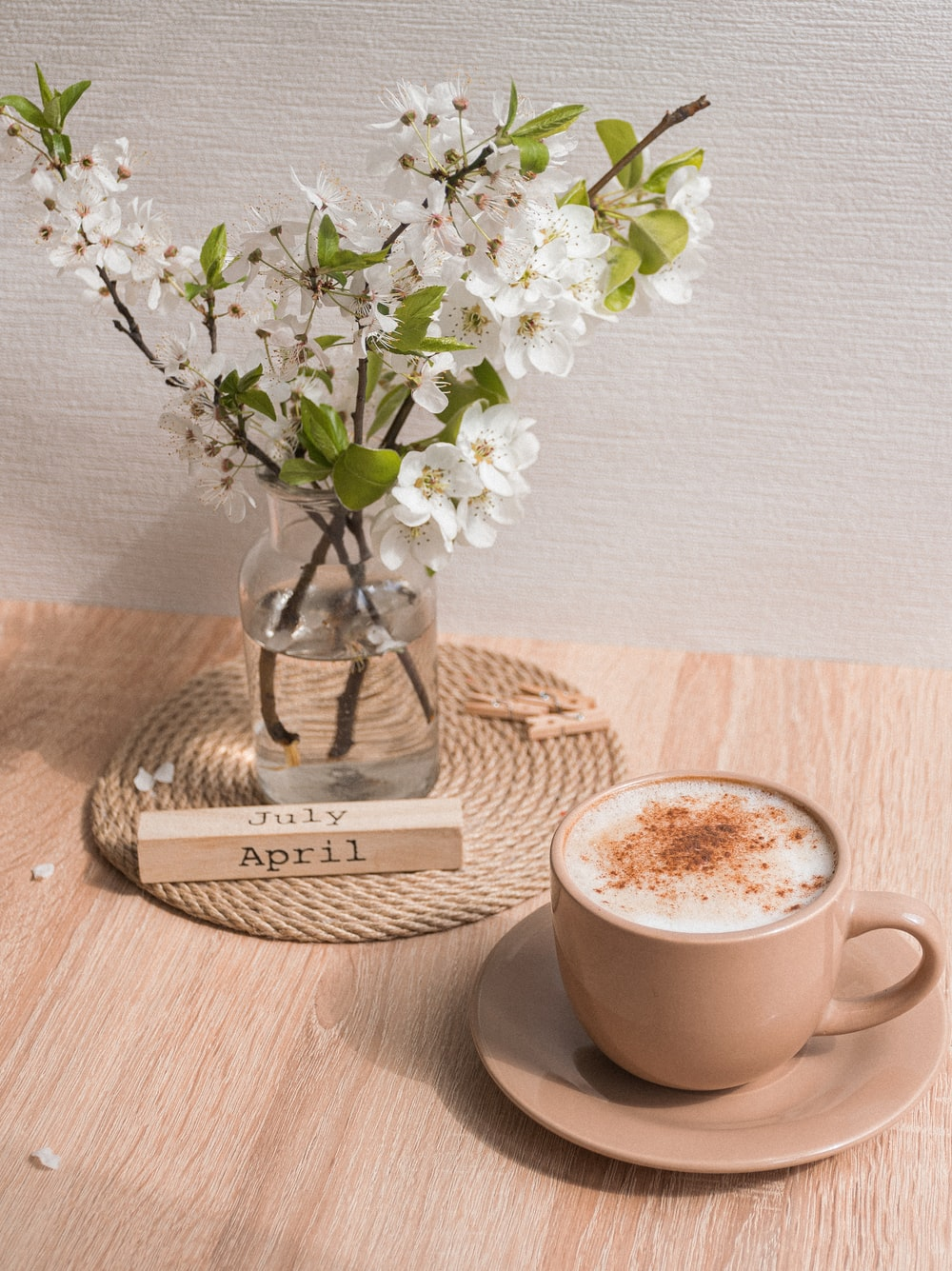 white ceramic cup with coffee on brown wooden coaster