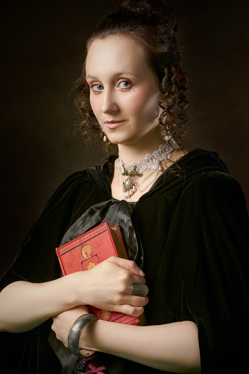 woman in black dress holding red book