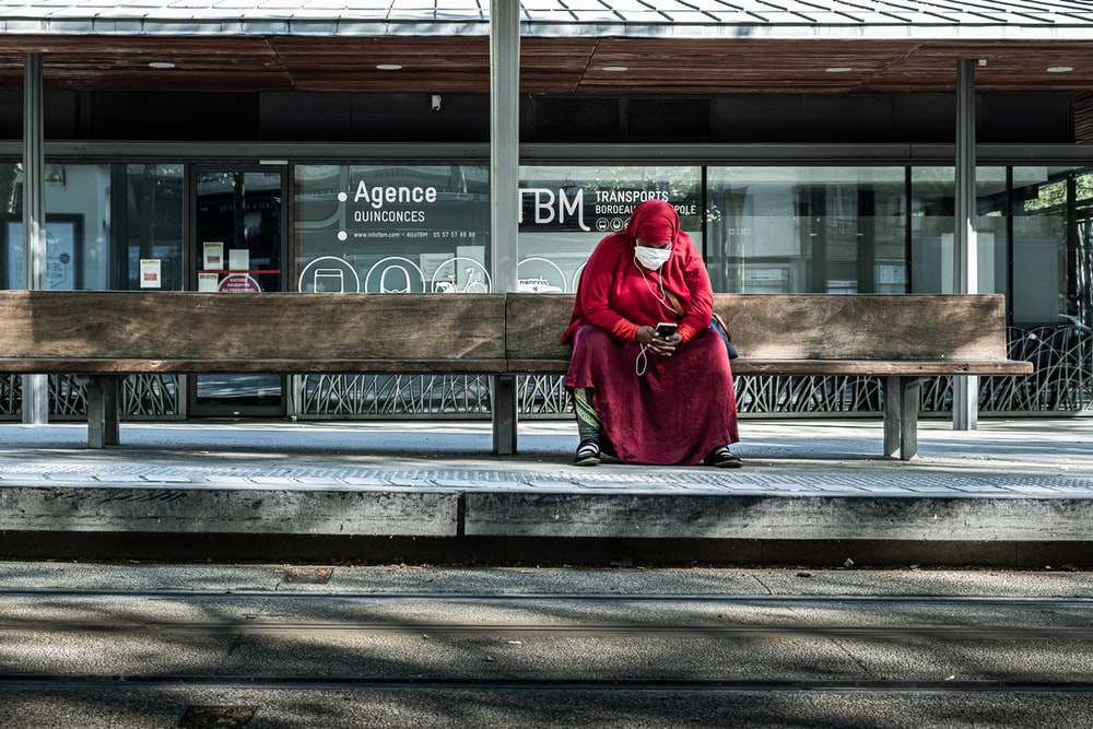 woman in red coat sitting on bench
