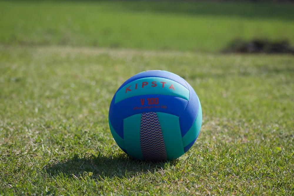 blue yellow and white soccer ball on green grass field during daytime