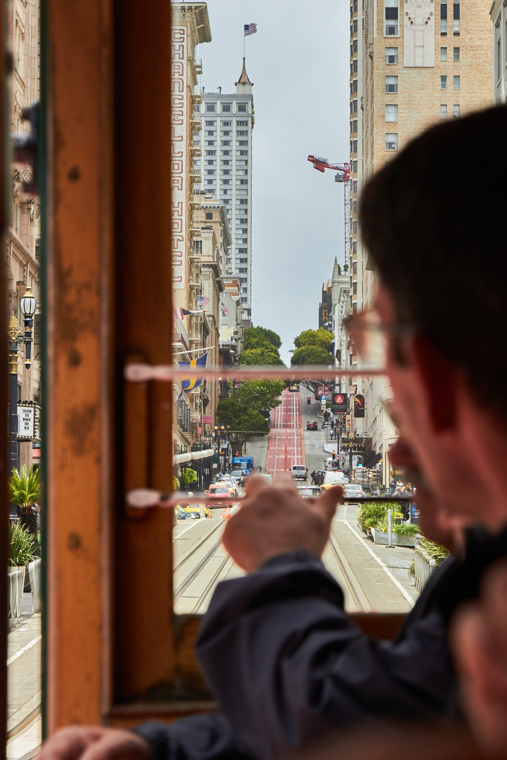 man in black shirt looking at the city during daytime