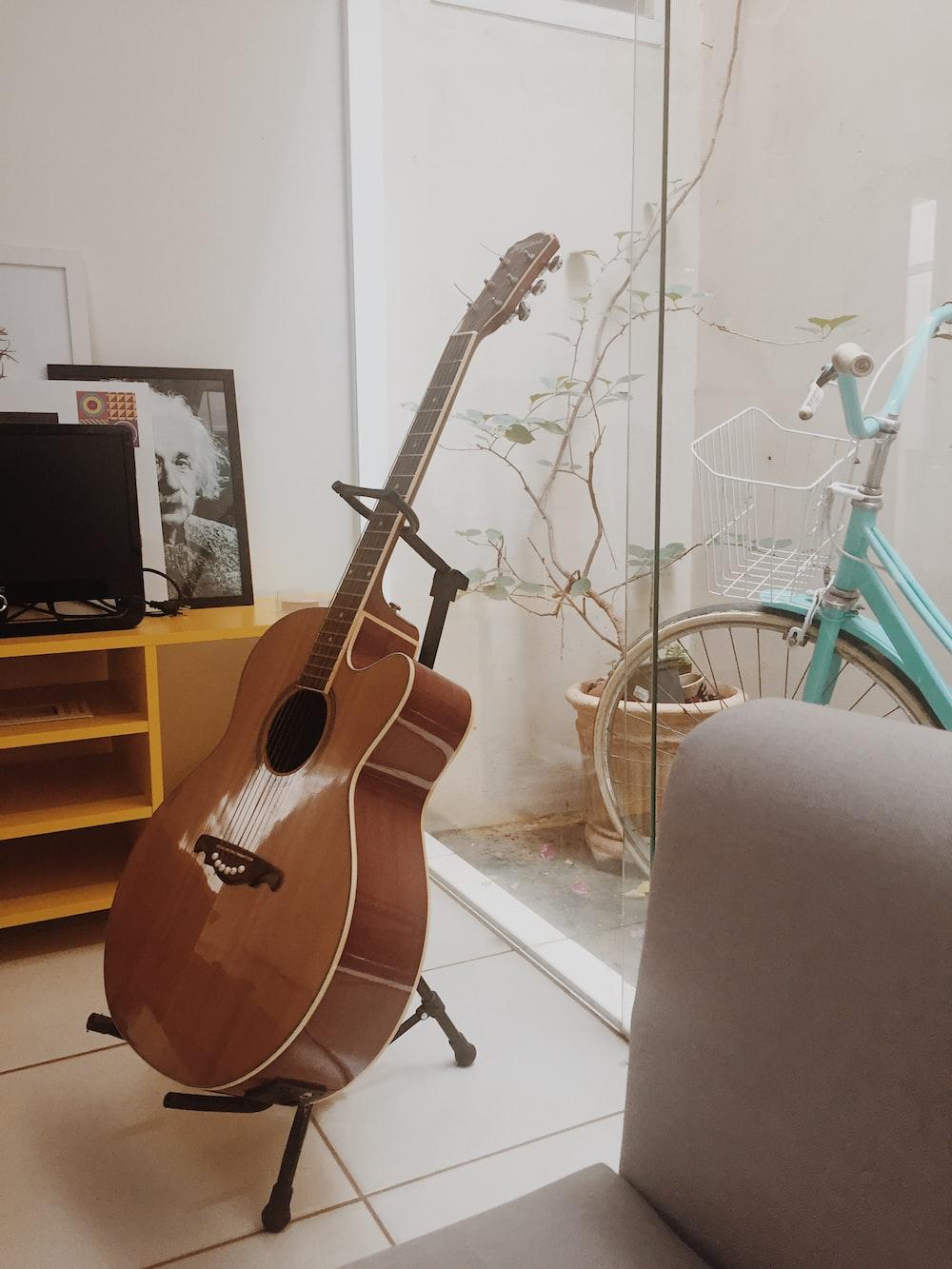 brown acoustic guitar on black steel stand