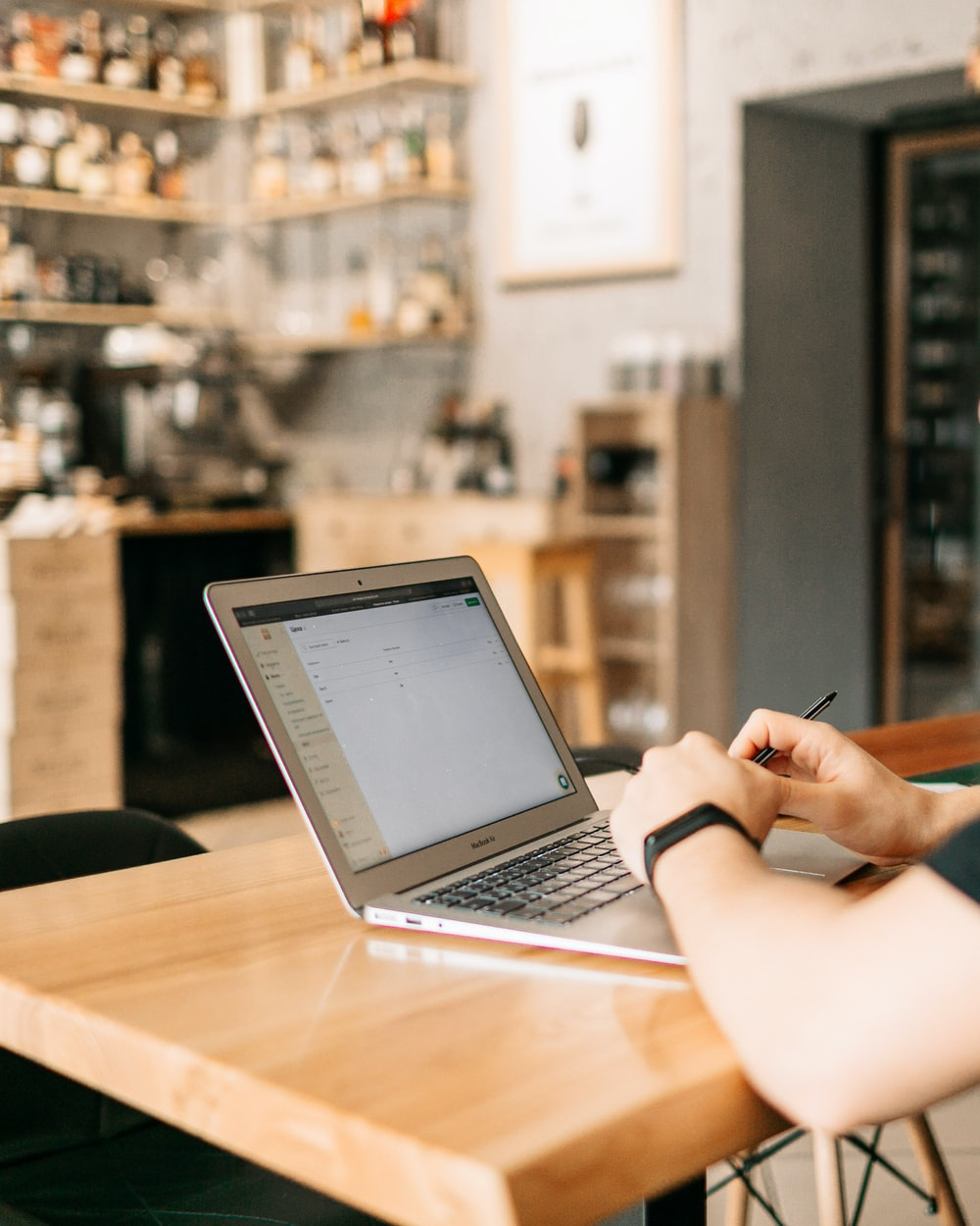person using macbook air on brown wooden table