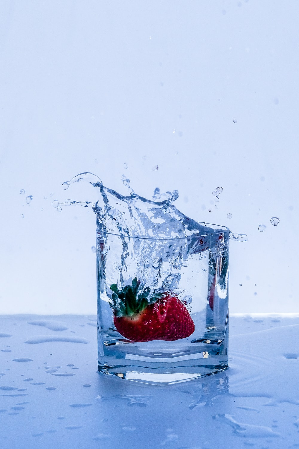 red strawberry in clear glass container