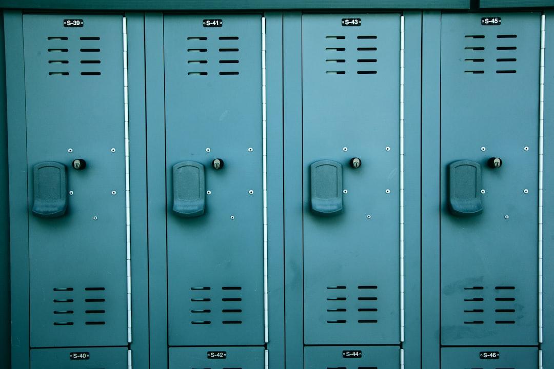 Teal blue metal wall lockers with numbers.