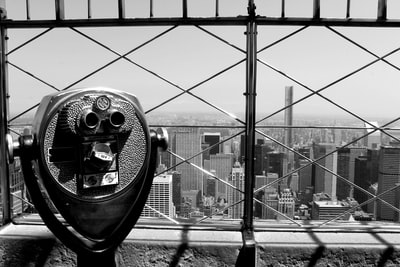 grayscale photo of coin operated telescope