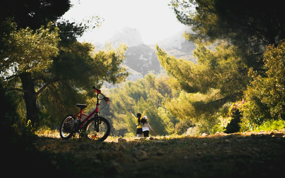 man and woman riding on red and black mountain bike during daytime