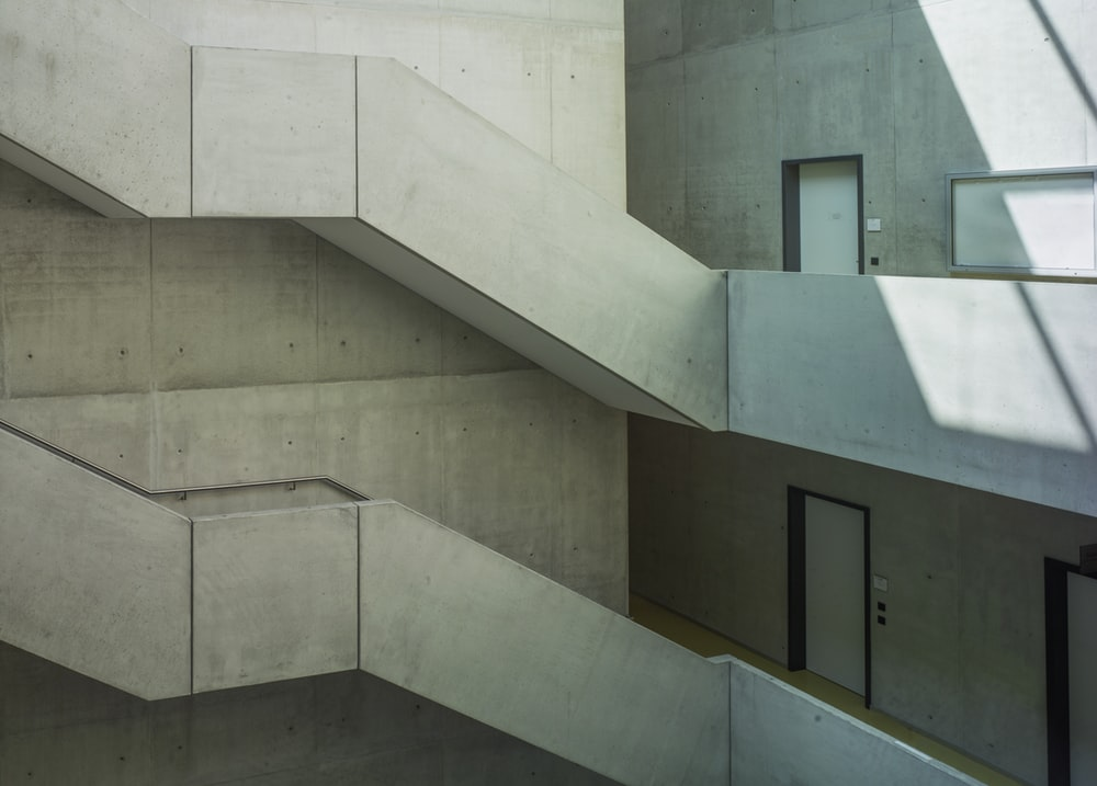 white concrete staircase with black wooden door