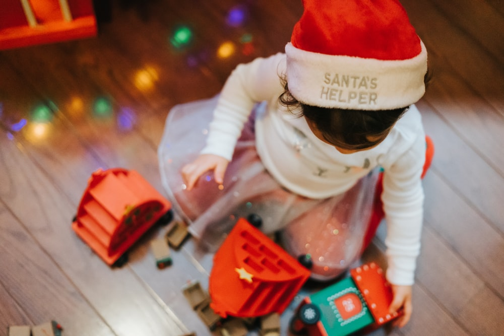 child in santa hat playing with lego blocks