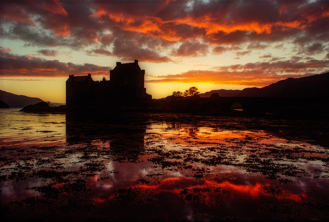 Sunset at Eilean Donan Castle, near Kyle of Lochalsh, Scotland. The clouds in the marshy lowtide made for a wonderful reflection. Shot on 35mm film.