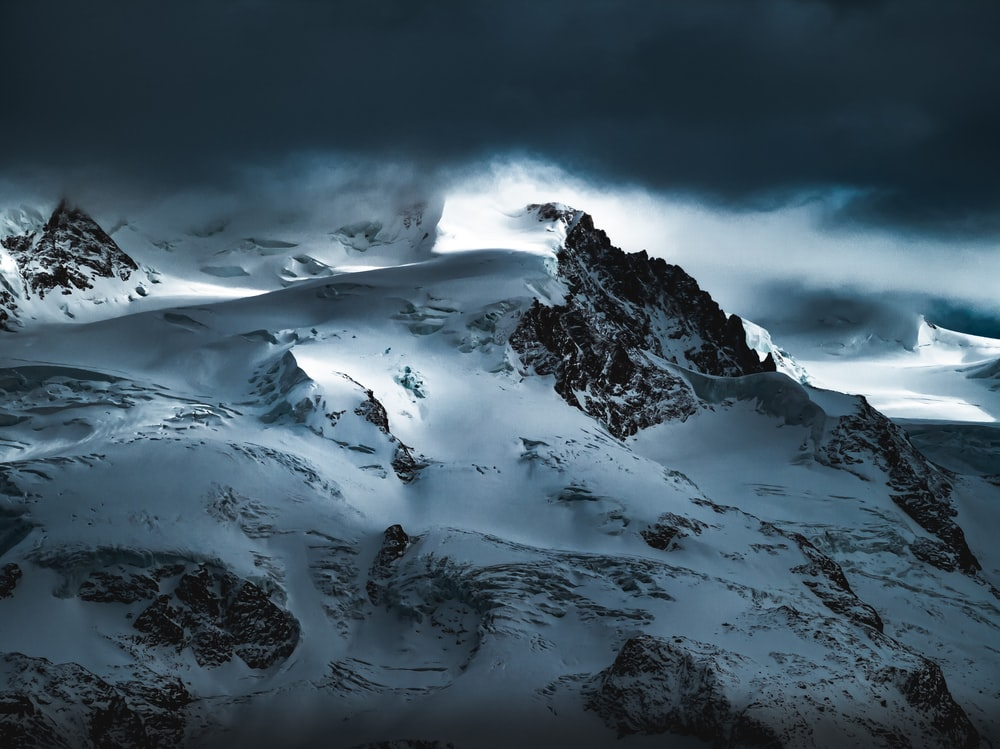 snow covered mountain under cloudy sky during daytime