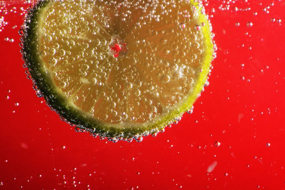 sliced lemon on red surface