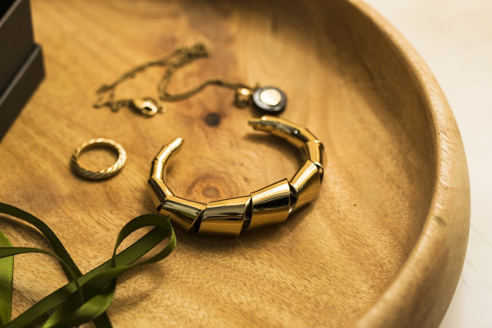 gold and green bracelet on brown textile