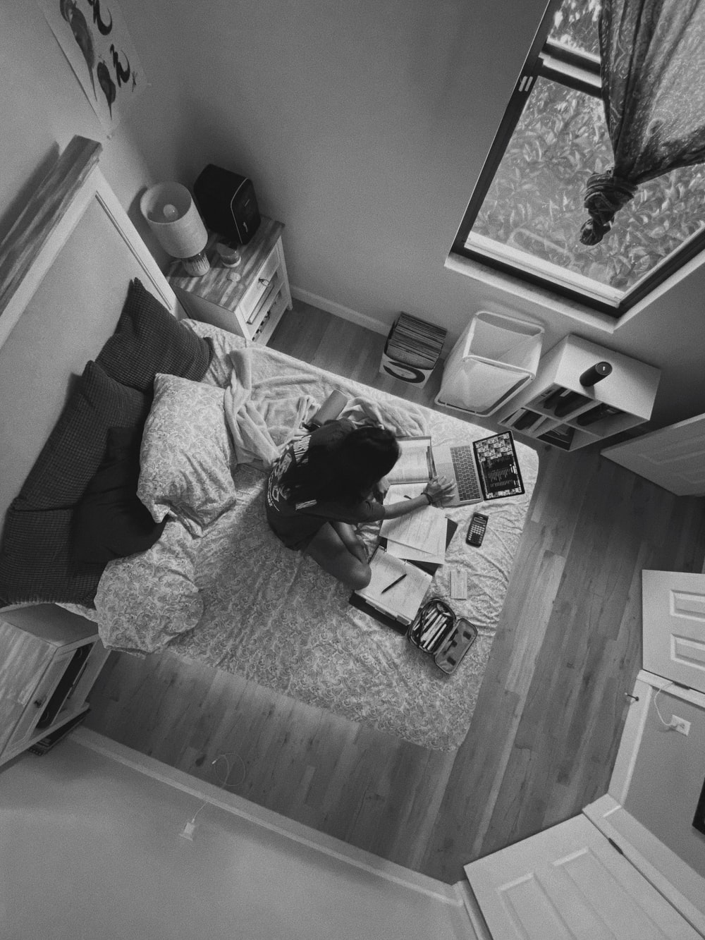 grayscale photo of woman lying on bed