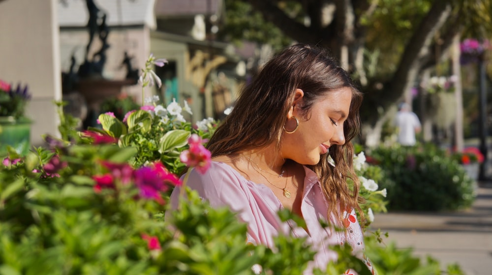 woman in white dress shirt holding pink flowers