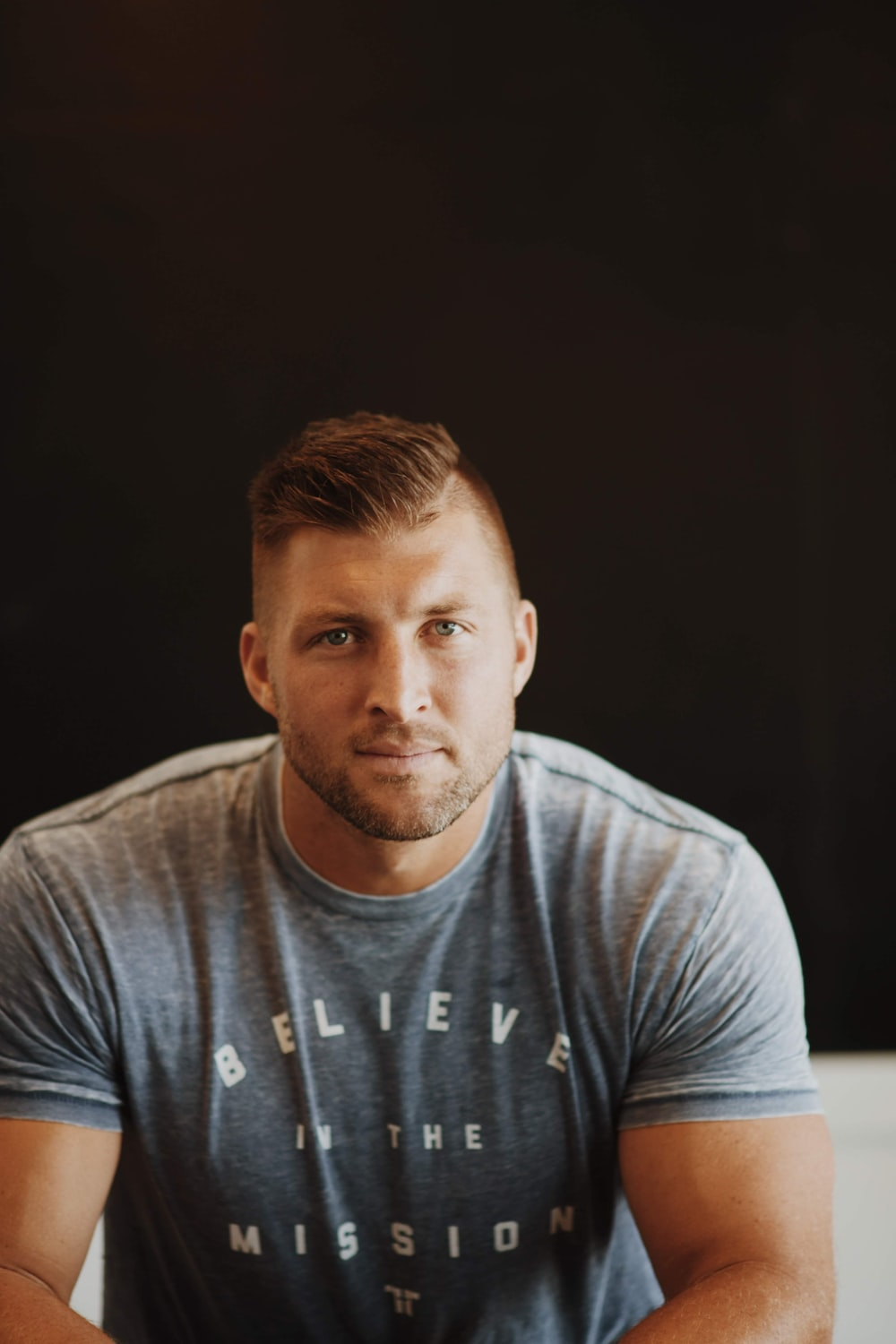 Tim Tebow in a gray crew neck t-shirt