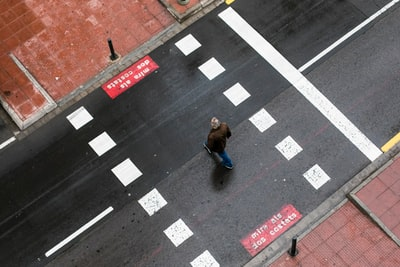woman in blue jacket walking on pedestrian lane during daytime asphalt teams background