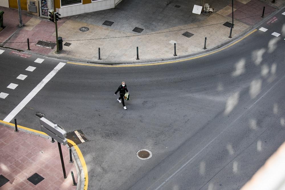 man in black jacket and black pants walking on sidewalk during daytime