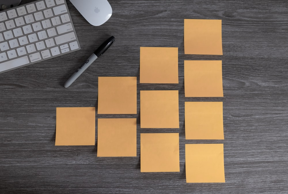 yellow sticky notes beside white apple magic mouse and white apple keyboard