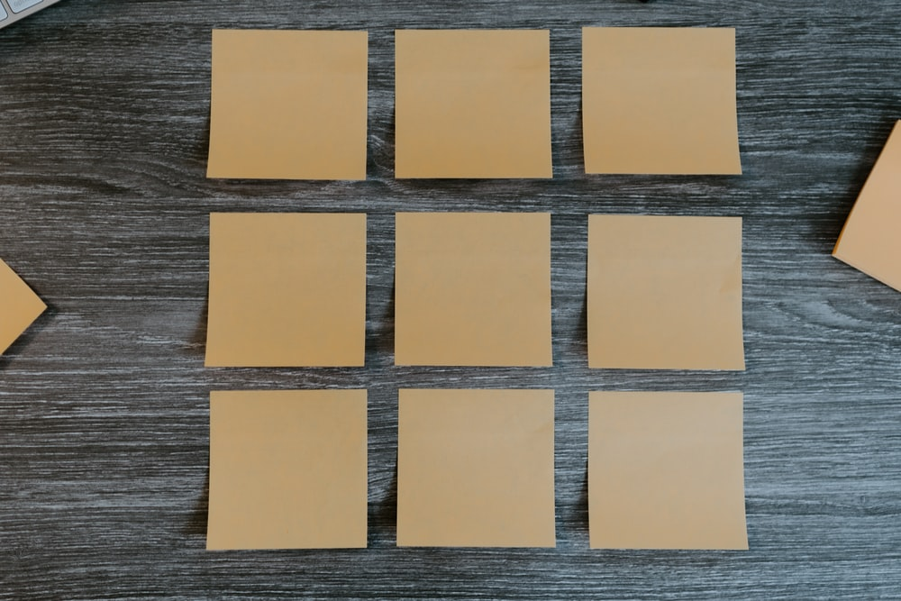 yellow sticky notes on brown wooden table