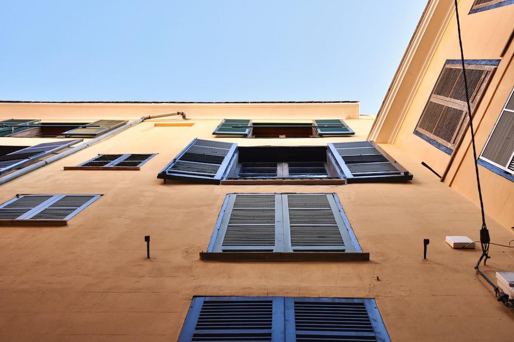 brown concrete building with blue windows