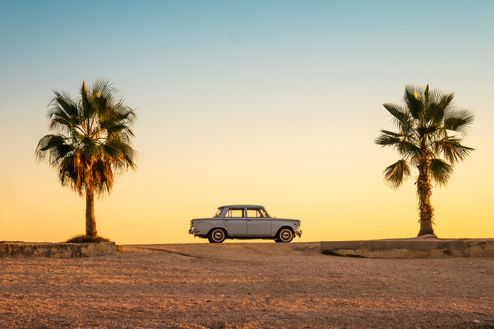 white and black car on brown sand during daytime