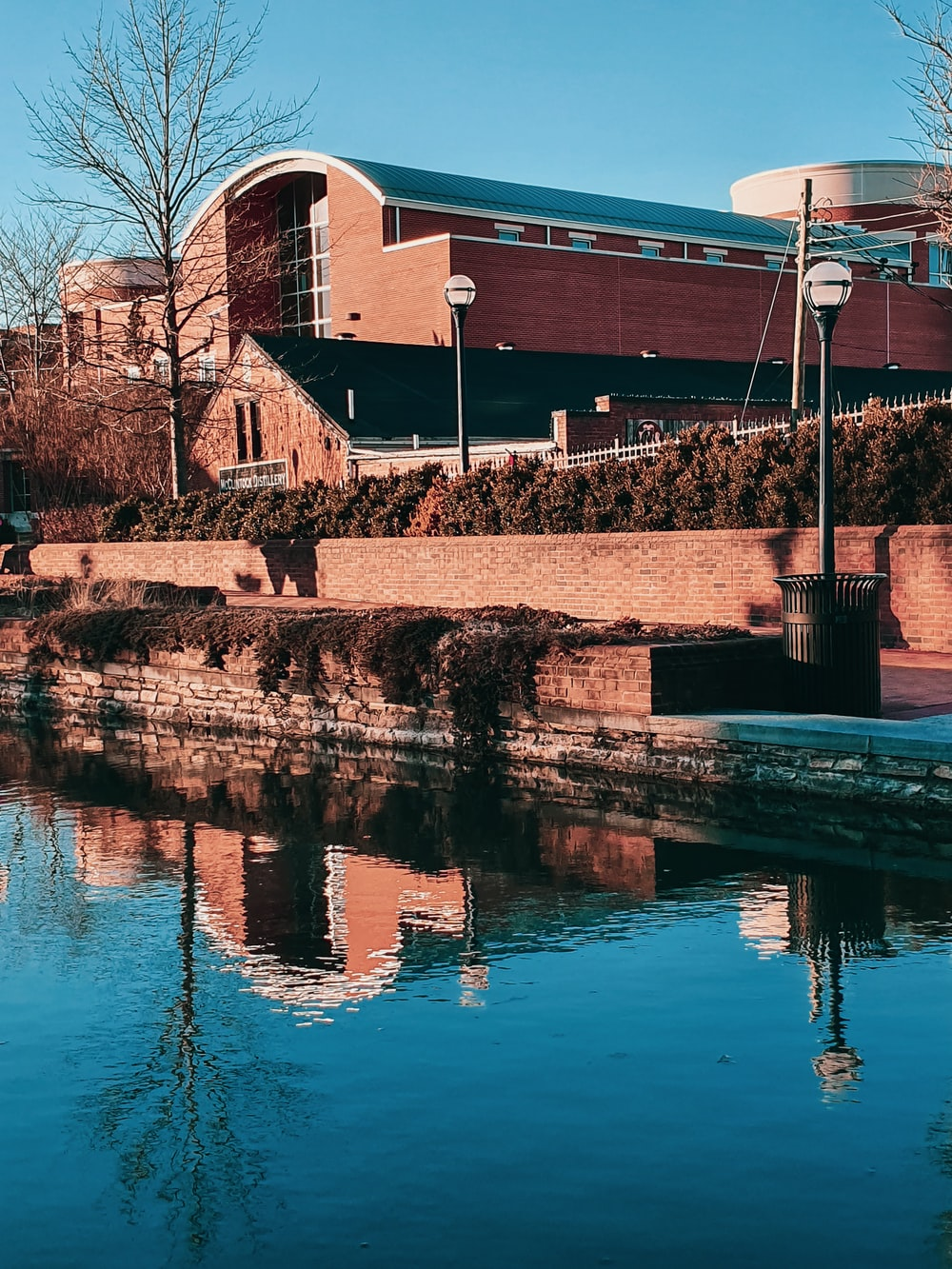brown brick building near body of water during daytime