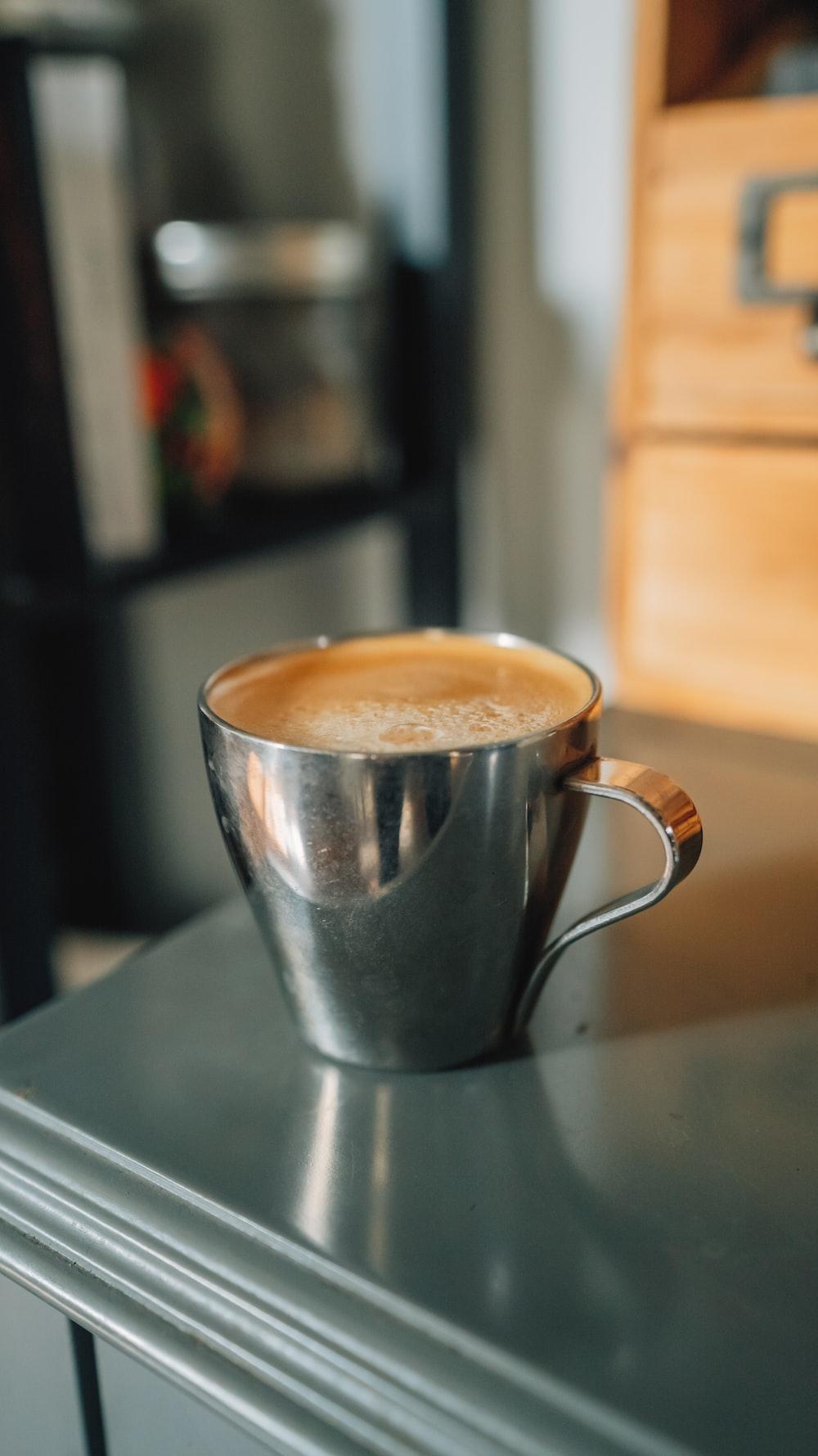 brown liquid in silver and white ceramic mug