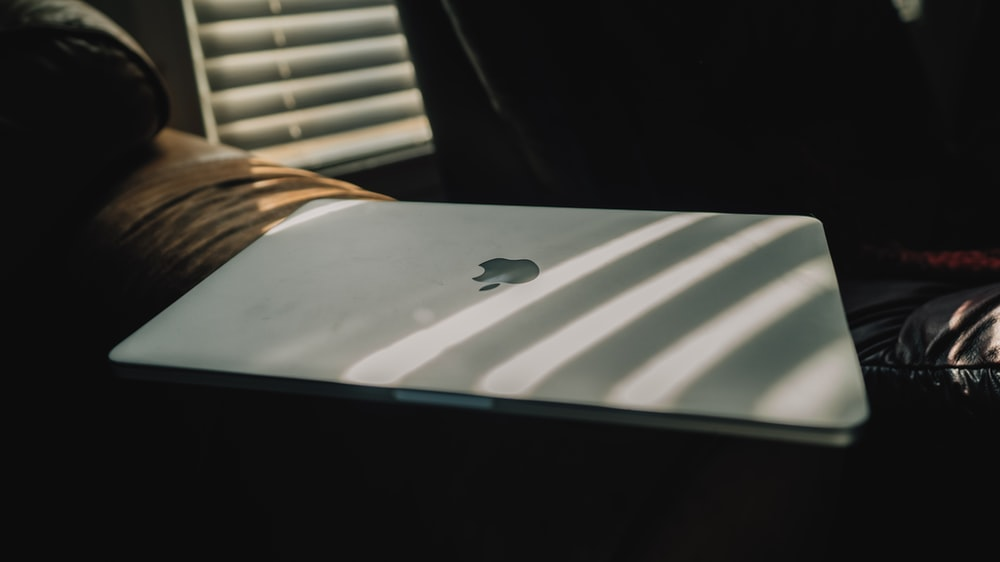 silver macbook on white table