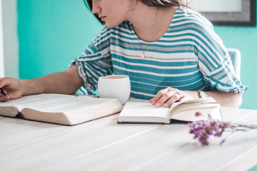 woman in blue and white striped shirt holding white ceramic mug