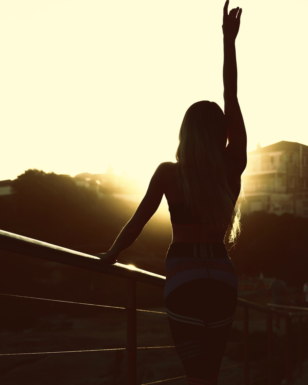woman in white tank top and black shorts standing on balcony during sunset