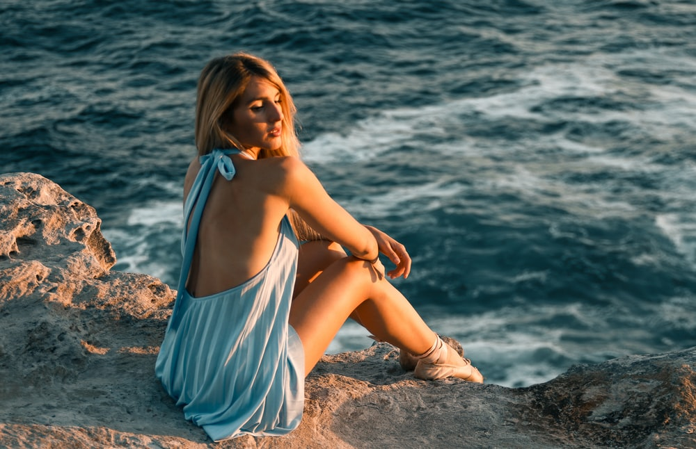 woman in white and blue stripe dress sitting on brown sand near body of water during