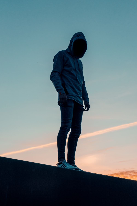 woman in brown hoodie standing on top of the building