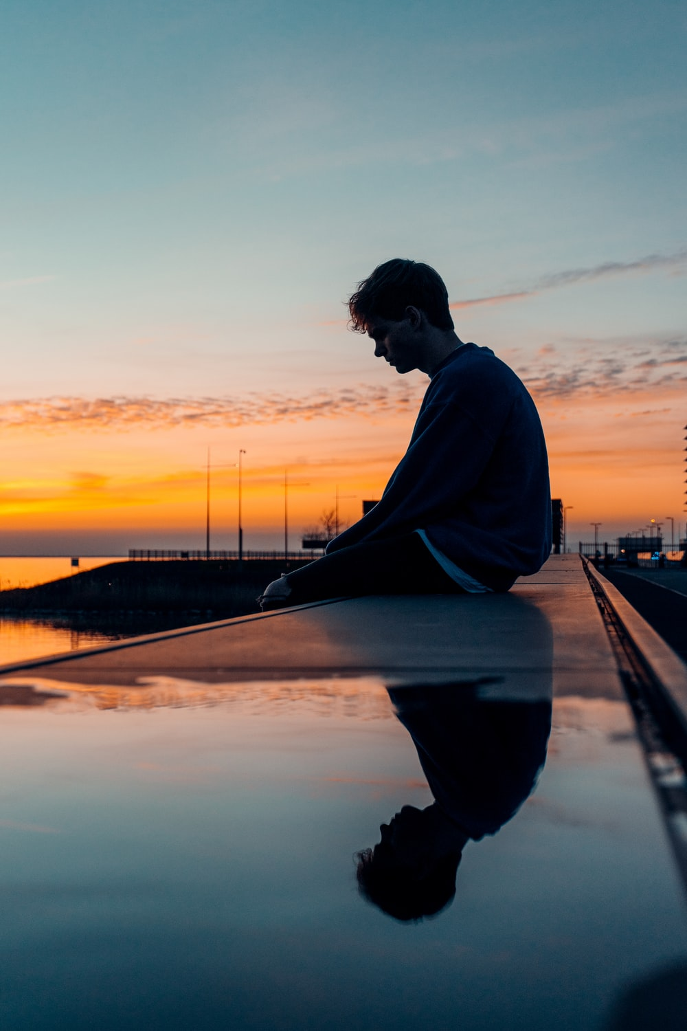 man in white long sleeve shirt and black pants sitting on dock during sunset