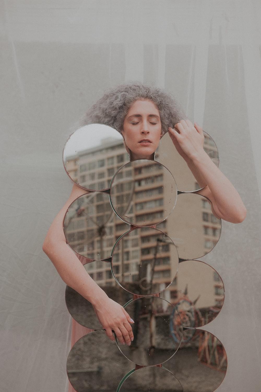 woman in black tank top holding mirror